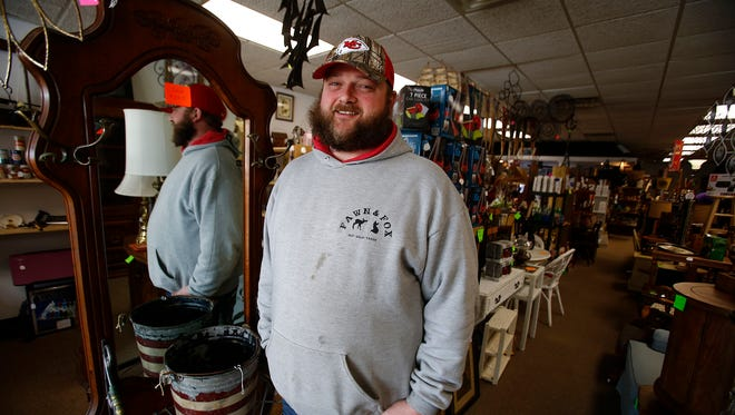 Mark McCaughey stands in his new store on the Indianola Square. Mark McCaughey owns the Fawn and Fox with his father Mac McCaughey. The store offers a wide variety of items ranging from collectible beer cans to antique furniture.