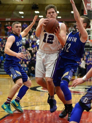 Albany's Kyle Birr (12) goes up between Braham's John Larson (20) and Kyle Johnson (12) in the first half of their Sect. 6-2A championship game Friday night, March 4 at Halenbeck Hall.