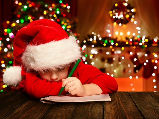 A little boy writing a letter to Santa Claus.