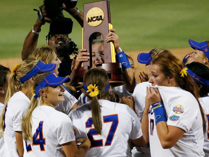 Florida pitcher Hannah Rogers holds the trophy as the team celebrates following an NCAA Women's College World Series softball tournament game against Alabama in Oklahoma City, Tuesday, June 3, 2014. Florida won the game 6-3 and took the title.