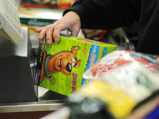 Michele Poss-Johnson, a cashier at Sunshine Foods, scans a customer's groceries on Wednesday, Jan. 28, at the store in Sioux Falls.