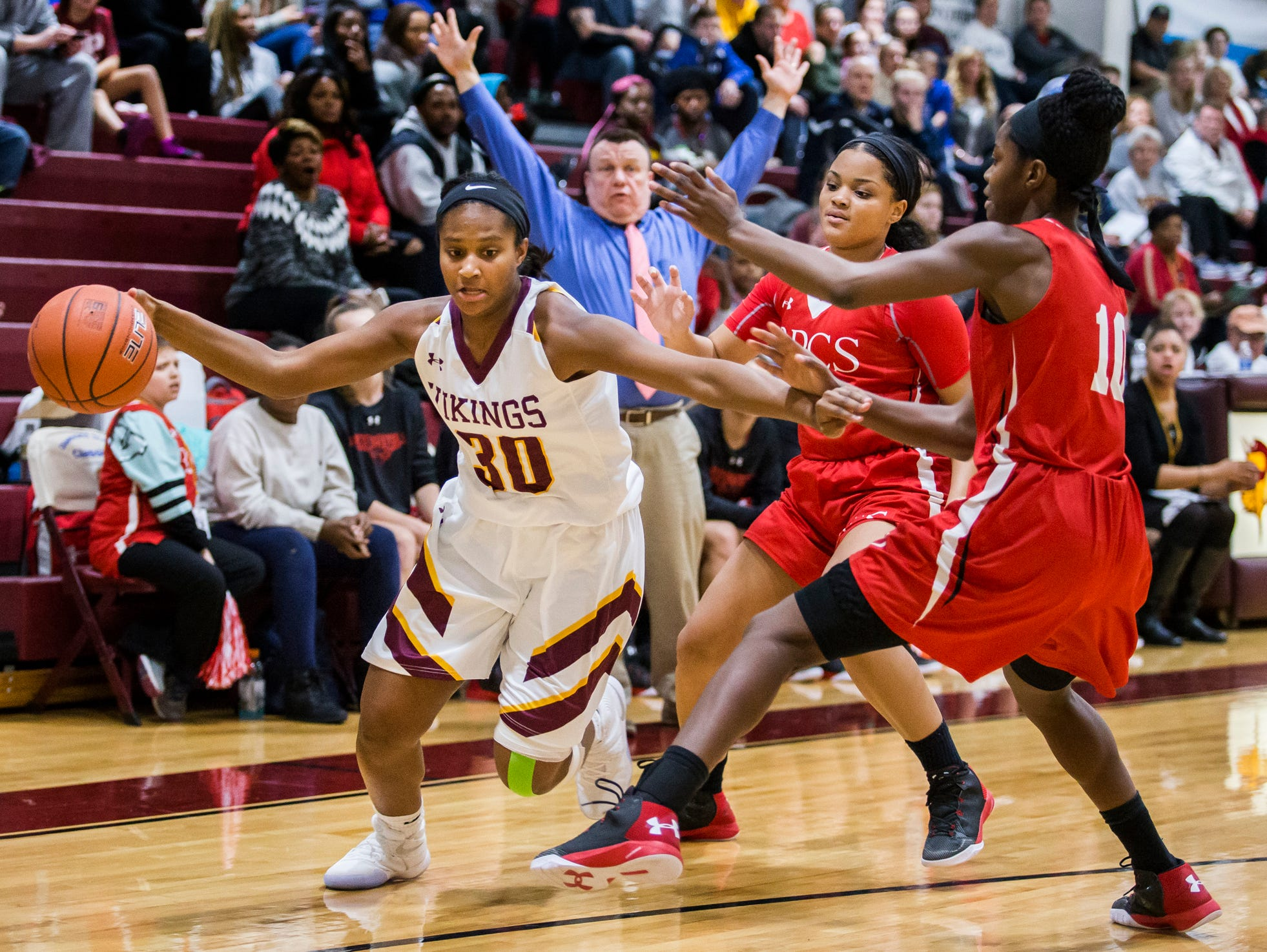 St. Elizabeth's Alanna Speaks (No. 30) drives to the basket against a pair of Roland Park defenders in the first half of St. Elizabeth's 58-44 loss to Roland Park Country School in the Diamond State Classic at St. Elizabeth High School in Wilmington on Tuesday night.
