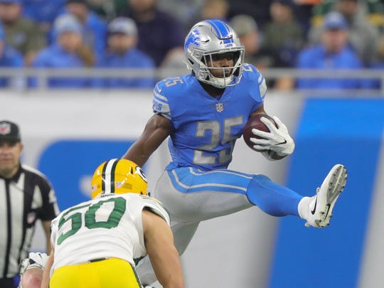 Lions' Theo Riddick hurdles a Packers defender in the