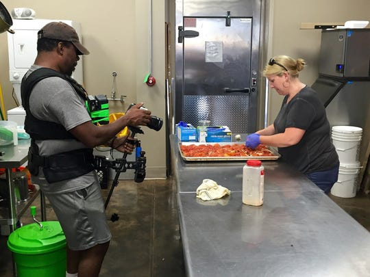 "A crew member from ""American Road Trip"" shoots Good People Kitchen owner Kate Dickey preparing food Monday. The Alexandria restaurant will be featured on the TV show, which is shooting its first season."