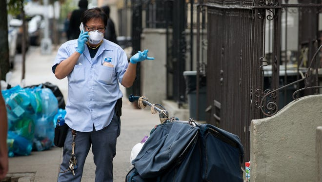 Postal Service worker Keven Ngo  in New York said he began wearing a mask after physician Dr. Craig Spencer was diagnosed with Ebola.