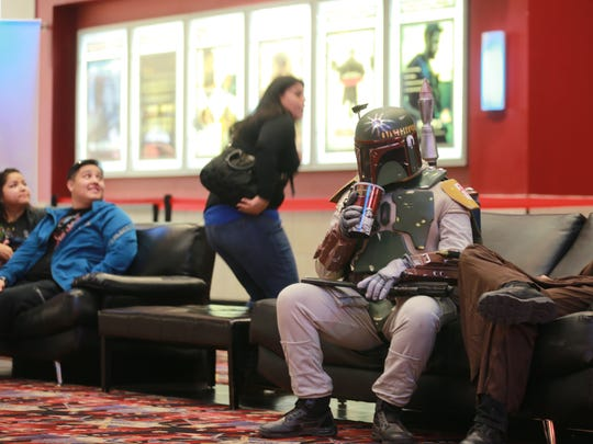 """Star Wars"" fan Roberto Alcazar enjoys a soft drink as he waits Thursday in the lobby of Premier Cinema + Imax at Bassett Place. He dressed as Boba Fett to watch the new movie, ""Star Wars: The Force Awakens."""
