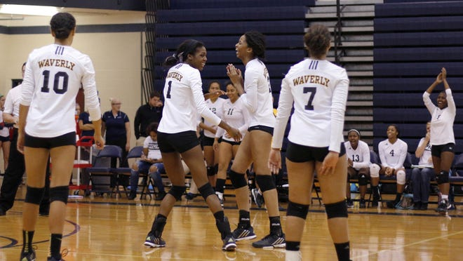 Waverly players, including Isbella Pizzo (10), Atiyaa Bolling (1), Alisia Smith and Angel Hague (7) celebrate after defeating Lansing Eastern in straight sets Tuesday, Nov. 3, 2015, in East Lansing, Mich.