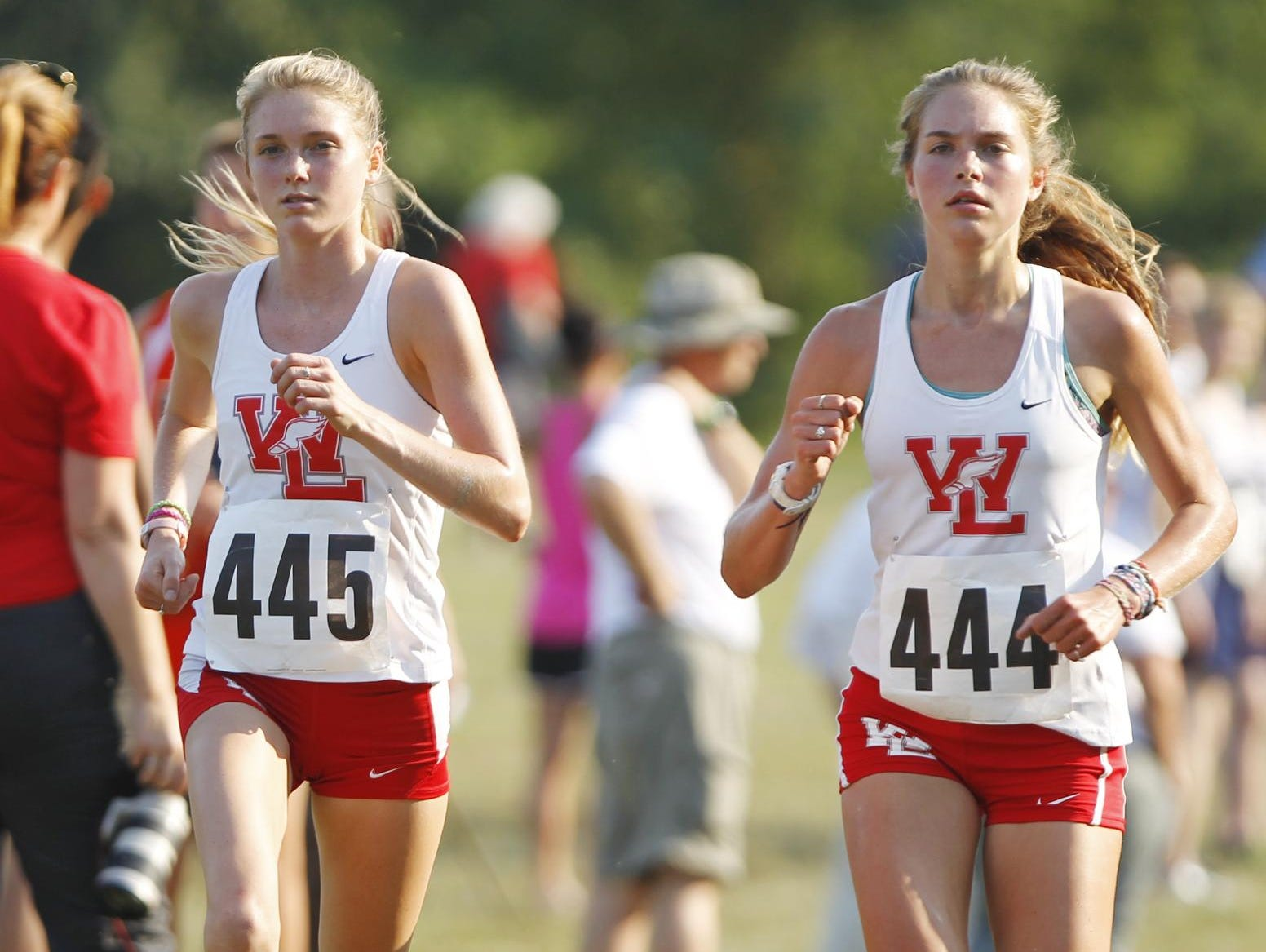 West Lafayette's Lauren Johnson, left, and sister Kristen run side by side to win the City County Cross Country meet Tuesday, September 1, 2015, at the Tippecanoe Amphitheater. Both girls finished with the time of 20:28, but Lauren was credited with first and Kristen second. The West Lafayette girls won the team competition with a score of 27 points. It is the sixth year in a row that the West Lafayette girls have won the City County Cross Country meet.