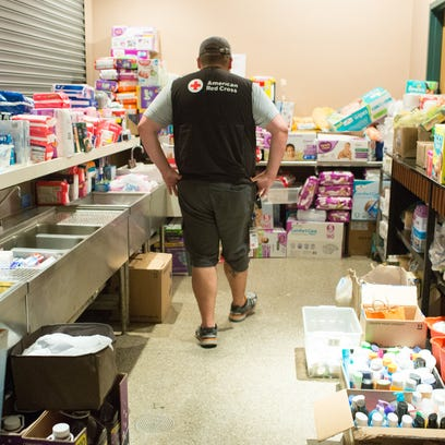 A volunteer looks over supplies at the Red Cross shelter