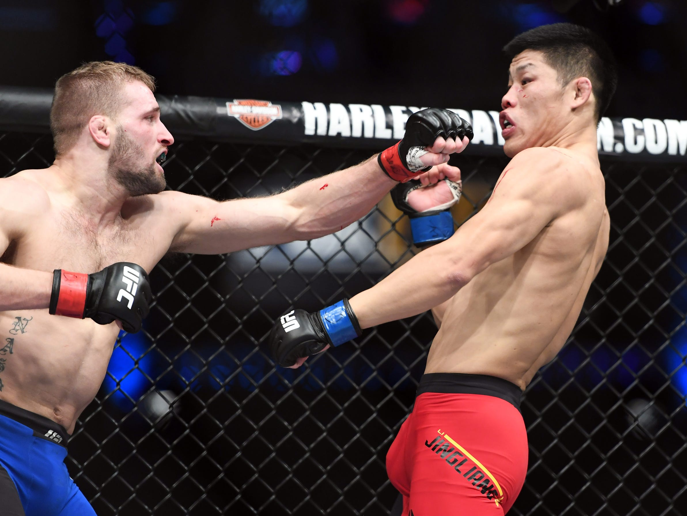 Bobby Nash (red gloves) competes against Li Jingliang (blue gloves) during UFC Fight Night at the Pepsi Center on Saturday.