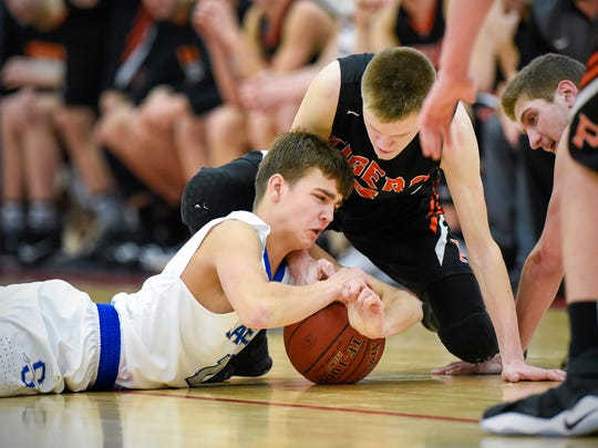 Sartell's Luke Tillotson battles for a loose ball with Princeton's Tate Laabs in overtime Friday, Dec. 29, during the Breakdown Granite City Classic boys basketball tournament at Apollo High School.