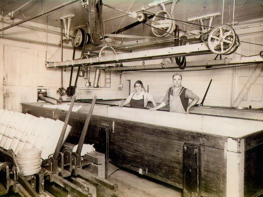 Frank and Marguerite Baker are pictured in the cheese factory. In 1937, wooden cheese vats were used and belt line shafts operated overhead.