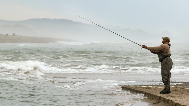 Phil Pope of McMinnville casts out into Siletz Bay as the high tide comes in while fishing for salmon Sept. 14, 2015, in Lincoln City.