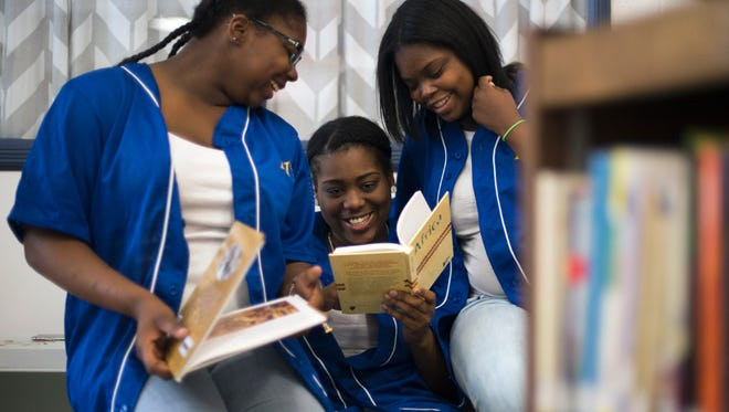 Millville seniors Quinteria Allen-Armstead, from left, Samira File and Daylisa Carter cram together with books as the school hosts a book fair conjunction with Books-A-Million Thursday, April 21 in Millville.