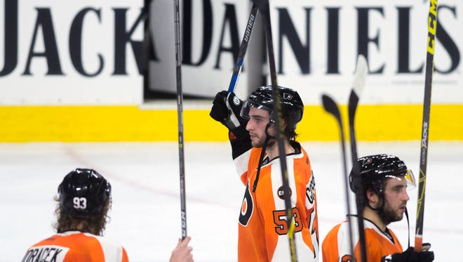 Flyers' Shayne Gostisbehere, center, raises his stick with fellow Flyers after a 1-0 loss Washington in game 6 Sunday, April 24 in Philadelphia.