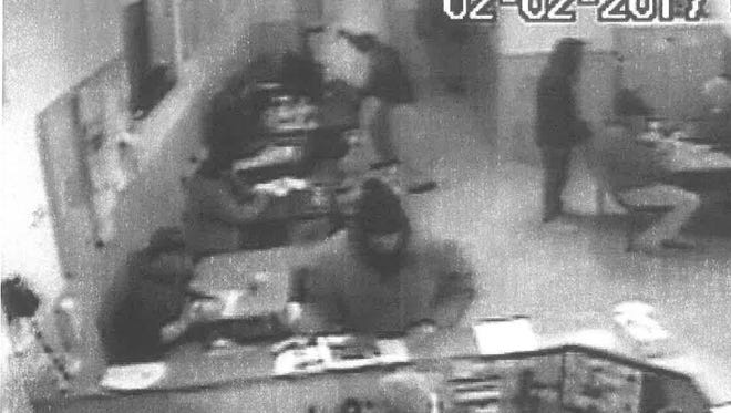 A still image from video surveillance at the Great Falls Rescue Mission shows a man wielding a knife toward a man's head near the back of the lobby. Law enforcement officials believe it was Stacy Trujillo who stabbed a man six times.