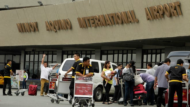Travelers and airport porters are seen in front of the Ninoy Aquino International Airport (NAIA).