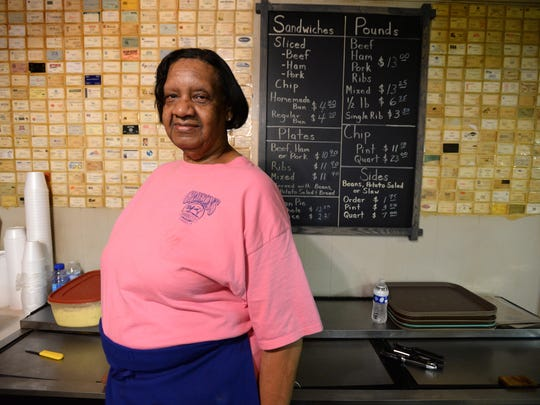 Lucille Pattain poses at the menu of Grayson's Barbecue where she has worked for 52 years.