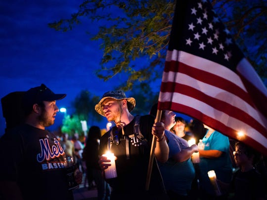 James Wrenn, left, and Mark Jory, holding flag, talk during the candlelight vigil for Mike and Tina Careccia at Pacana Park in Maricopa on Friday, July 3, 2015.