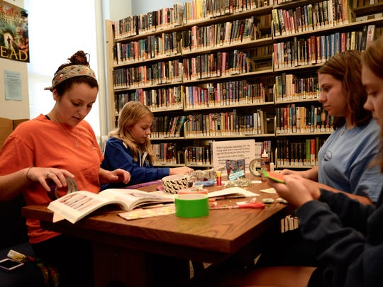 From left to right: Emily King, Olivia King, Olivia Huffman and Mary Jones do crafts at the Staunton Public Library on Sunday, Sept. 13, 2015. This is the first Sunday the library has had hours in almost a decade.