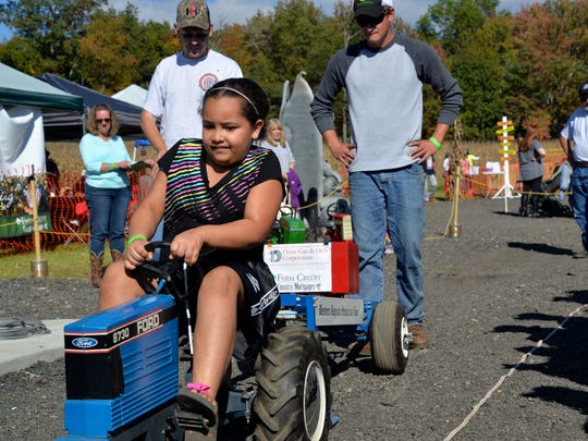 A participant tries to get the gold in the children's tractor pull during the Farming in the Valley event outside of Waynesboro on Sunday, Oct. 13, 2015.