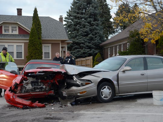Officers from Manitowoc Fire Department and Manitowoc Police Department investigate and clean up at the scene of a two-car accident at the intersection of Spring and Huron Streets Friday, Nov. 13.