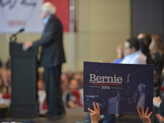 A supporter waves a campaign sign as Sen. Bernie Sanders gives his speech at a campaign rally in Cedar Rapids, Iowa, on Saturday, January 30, 2106.