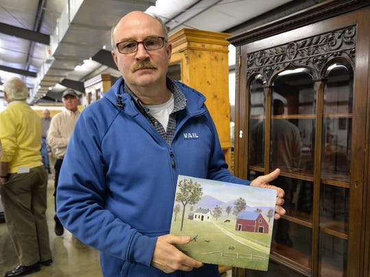 Jeff Bradfield, of Harrisonburg, with a Grandma Moses painted he place a bid on at the Bennett Auction at Augusta Expo on Sunday, Jan. 31, 2016.