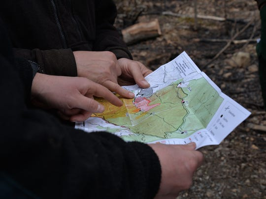 George Washington and Jefferson National Forest workers look at a map of the affected wildfire areas at St. Mary's Wilderness.