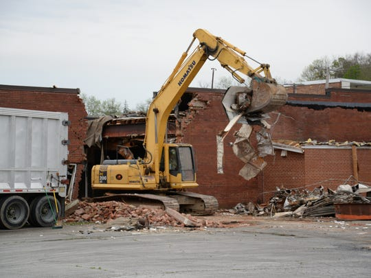 Crews demolish a building, owned by DuPont Credit Union, along Central Avenue in Staunton in May 2014.