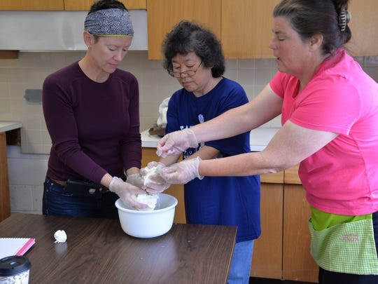 From left to right: Students Cinda Malouin and Sayoko MacDougall with instructor Sharon Munyak pull mozzarella during a cheese making class at Rosenwald Community Center in Waynesboro on Sunday, May 1, 2016.