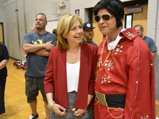 In this May 20, 2016 photo, incoming Wicomico County public schools Superintendent Donna Hanlin gets a laugh about James M. Bennett High School math teacher Stewart Soper's Elvis costume during the school's Lip Dub video production day.l Both participated in the end-of-school production that is to be posted on YouTube.