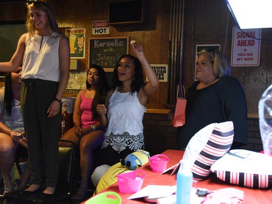 Morgan Dominguez, 17, (center) calls out a winning ticket for prizes at a fundraiser for her trip to London held at Beer Thirty's in Port Clinton on Wednesday. Dominguez made the United Cheerleading Association team and will be participating in the New Year's Day parade in London, England, in front of the Royal Family.
