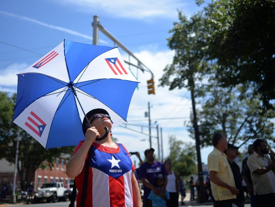 A spectator looks up as the Puerto Rican flag is raised