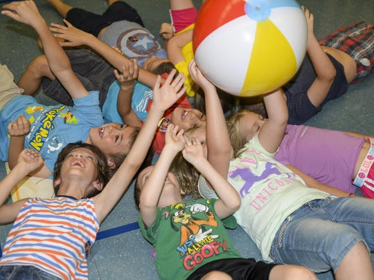 A group of children attending the base chapel's vacation bible school toss a ball over their heads in an effort to keep it from hitting the ground as part of a game at Holloman Air Force Base on July 19. Children attending the VBS program participate in a variety of activities, ranging from science experiments to arts and crafts.