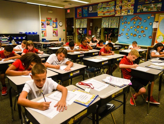 Fourth grade students fill out info sheets during the
