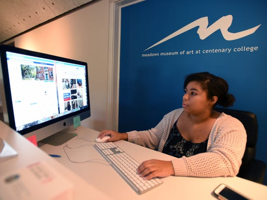 Chelsea Perry works on the Meadows Museum's social media pages from the museum's receptionist desk.