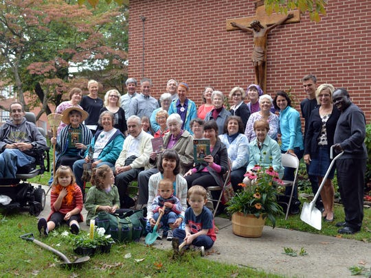 Members of St. Rose of Lima's garden group, including some very young volunteers, gather at the church gardens in Haddon Heights. More than 6 dozen helpers, from age 2 to 95, have transformed a once shabby and root-tortured area outside the church into a peaceful paradise that calls visitors to meditate.
