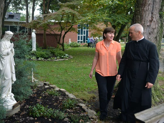 Mary Needham of Audubon talks with Father Joseph Byerley; she donated the Immaculate Conception statue for the gardens at St. Rose of Lima in Haddon Heights.