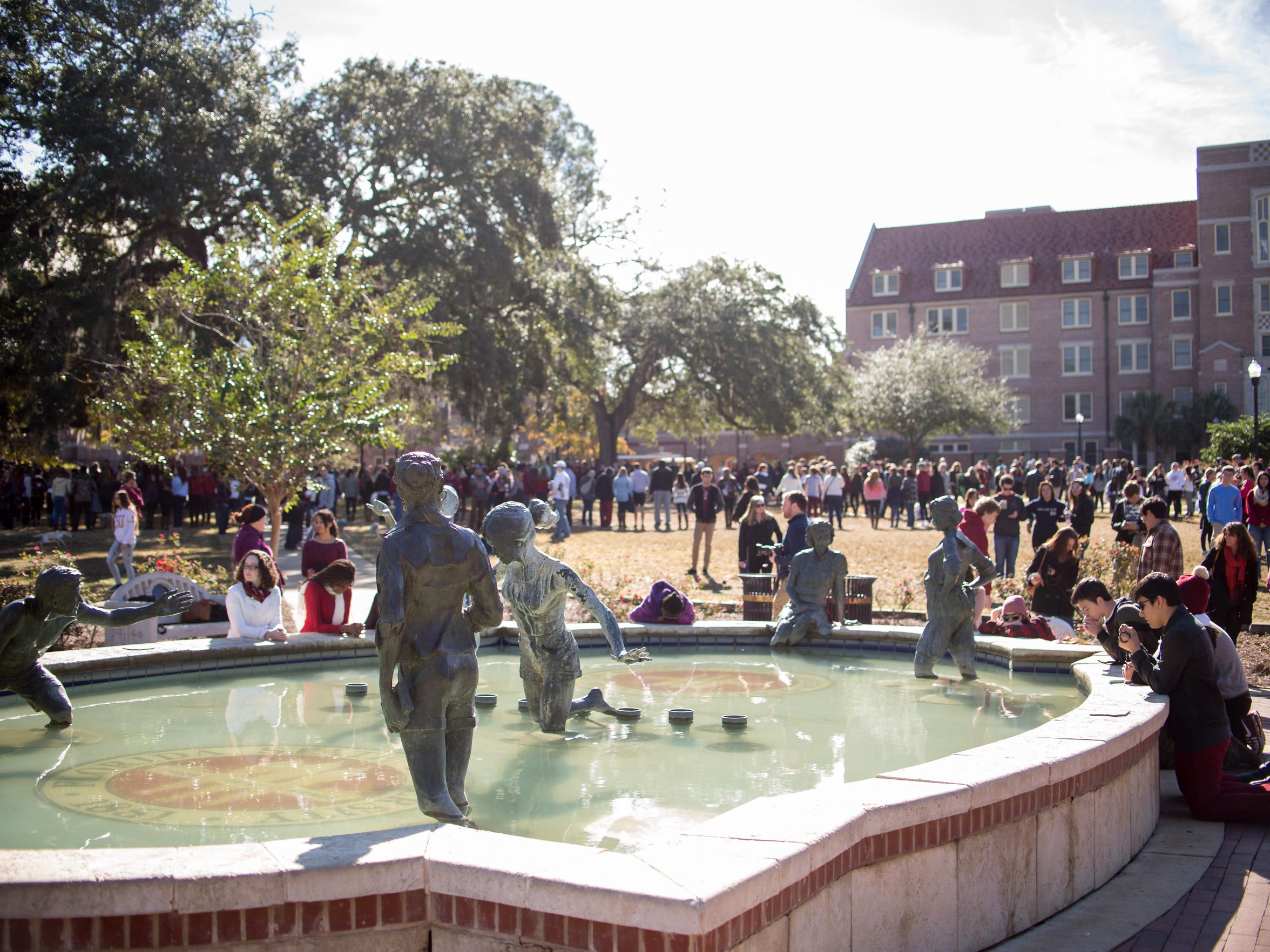 Students, some in prayer, gathered around Legacy Fountain