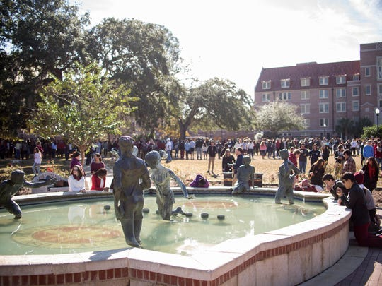 Students, some in prayer, gathered around Legacy Fountain on Landis Green the day after the shooting in Strozier.