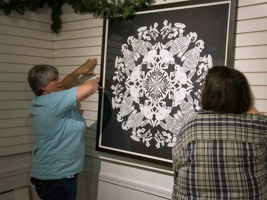 Mary Gaynier, left, hangs one of her paper snowflakes in the Hayes Train Special display area.