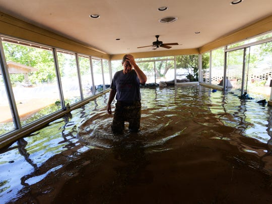 "Caddo Parish Sheriff Steve Prator stands in his home which has about 15"" of water."