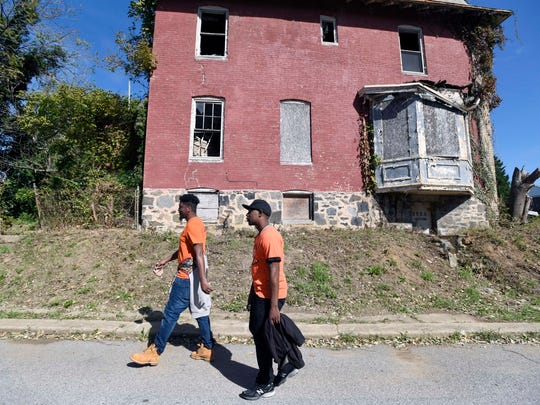 In Baltimore's Park Heights area, Paul Frazier, left, and Damian McNeil walk the streets daily as part of their jobs with Safe Streets. McNeil is intimately acquainted with the neighborhood; he used to deal drugs there. Now he watches out for it, making sure any beefs are handled without guns.