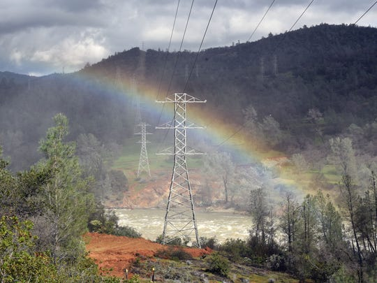 A rainbow arches above the Feather River where it crosses beneath power lines beneath the Oroville Dam. Workers severed the lines during the flooding fear, worried that a flood could rip out both lines and towers, causing even more damage.