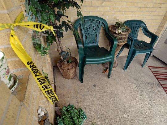 Police tape hangs by the front door of Ludella Scott's
