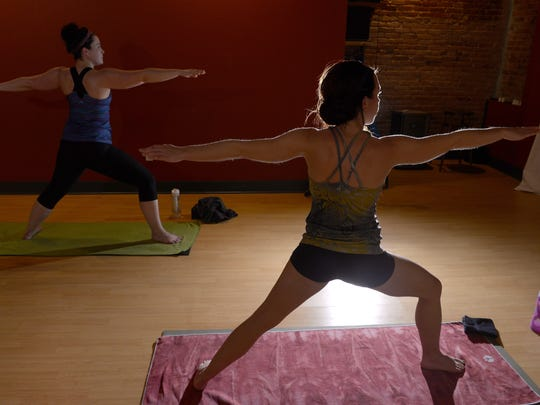 Kaitlyn Reed, behind, follows the lead of yoga instructor Courtney Grove, foreground, in a hot yoga class at the Firefly Hot Yoga Bar in downtown Lansing.