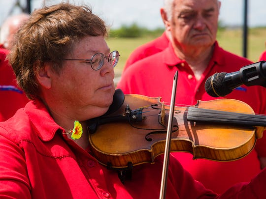 Dorothy Douthit of Fiddle Fire Cafe plays taps during the rededication ceremony at the Vietnam Veterans Memorial.