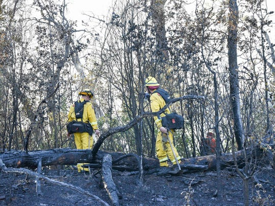Cal Fire firefighters take a break from working a vegetation