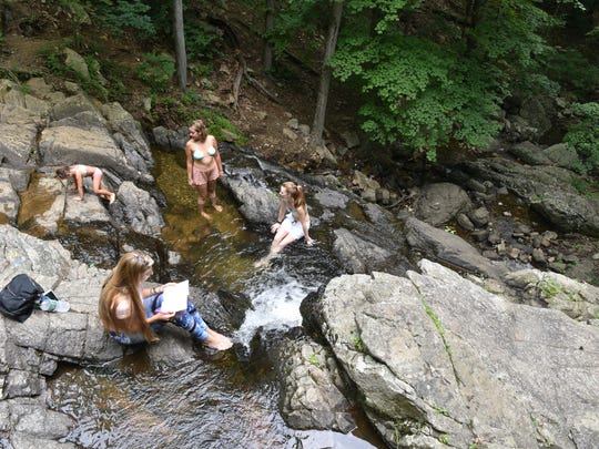 People cool off at  natural pool atop a waterfall at the Ramapo Valley County Reservation.